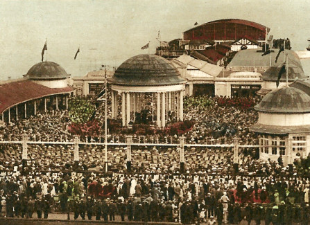Hand-tinted postcard of the bandstand on a busy day