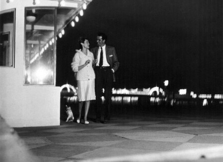 Couple strolling on the promenade at night, 1960s