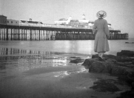 Woman in hat and coat on the beach by the Pier