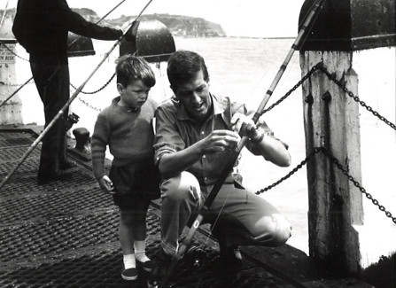 Father and son fishing from the landing stage, 1960