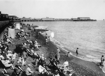 Holidaymakers on Hastings beach with the Pier in background, 1920s