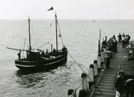 A fishing boat passing by the landing stage of the Pier
