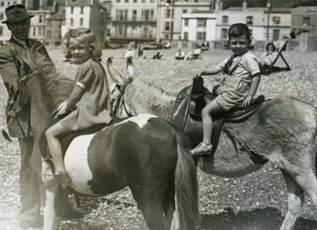 August bank holiday weekend 1945, children enjoying donkey and pony rides on Hastings beach.