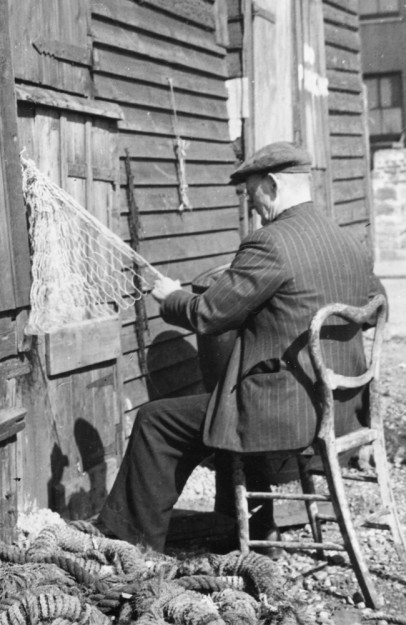 A fisherman making nets by the net huts | Image reproduced with permission of Hastings Museum and Art Gallery