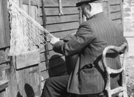 A fisherman making nets by the net huts