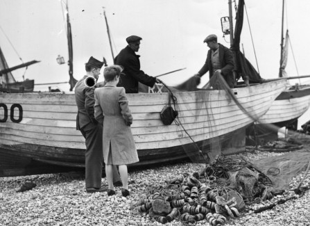 A publicity shot of a WWII soldier and girlfriend visiting the fishing boats in Hastings