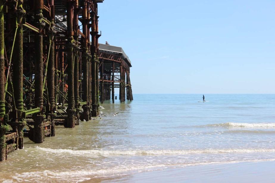 Paddle boarder near pier