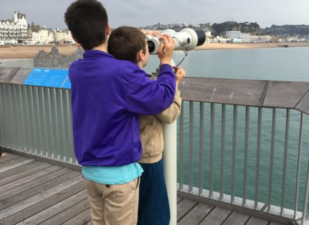 James and Nicky looking through telescope at Hastings Pier.