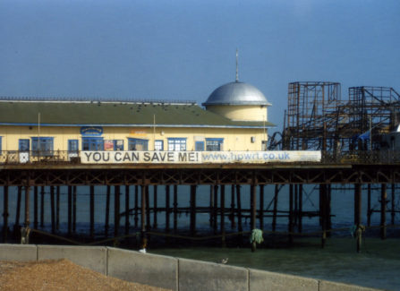 """The Pier after the fire with """"You can save me"""" banner"""